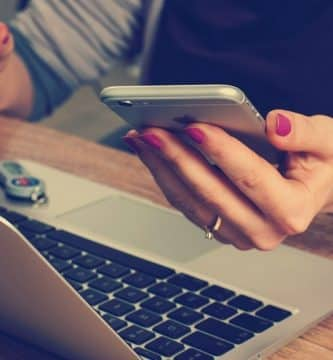 Mujer sosteniendo un móvil con un ordenador apoyado en la mesa